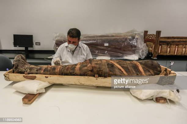 An Egyptian archaeologist works on a mummy during a restoration process at the restoration lab of the newlybuilt Grand Egyptian Museum in Giza...