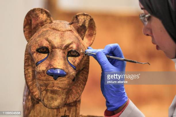 An Egyptian archaeologist works on a pharaonic bed with animal figures which belonged to King Tutankhamun during a restoration process at the...