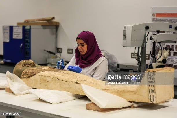 An Egyptian archaeologist works on a sarcophagus which belonged to King Tutankhamun during a restoration process at the restoration lab of the...