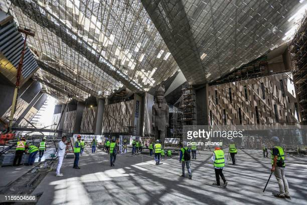 August 2019, Egypt, Giza: Workers stand near a giant statue of the Egyptian pharaoh Ramses II in hall of the Grand Egyptian Museum in Giza outside...