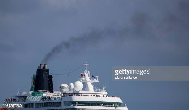 August 2019, Mecklenburg-Western Pomerania, Rostock-Warnemünde: A dark cloud of smoke rises from the chimney of a cruise ship as it enters the port...
