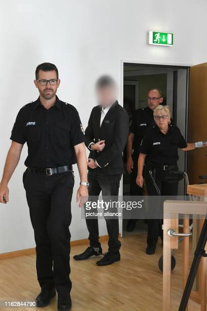 August 2019, Mecklenburg-Western Pomerania, Stralsund: The 21-year-old defendant is handcuffed and footcuffed to the courtroom of the Stralsund...