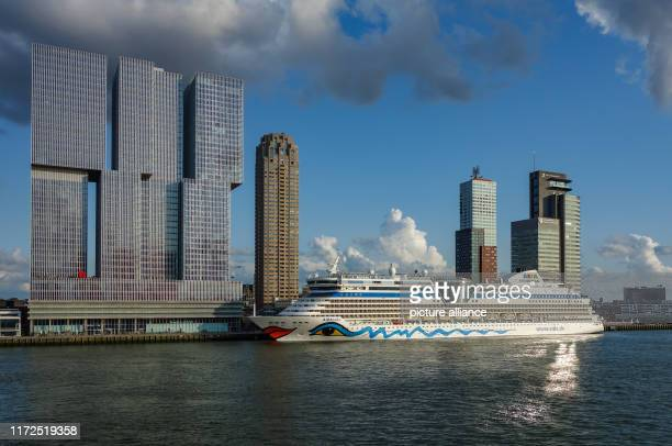 The cruise ship AIDAbella is situated at the harbour at the river Nieuwe Maas in front of skyscrapers Photo Patrick Pleul/dpaZentralbild/ZB