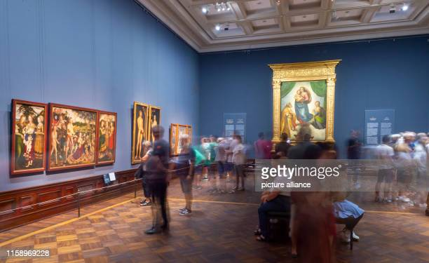 "August 2019, Saxony, Dresden: Numerous visitors are looking at Raffael's work ""Sistine Madonna"" in the exhibition ""Highlights of the Old Masters..."