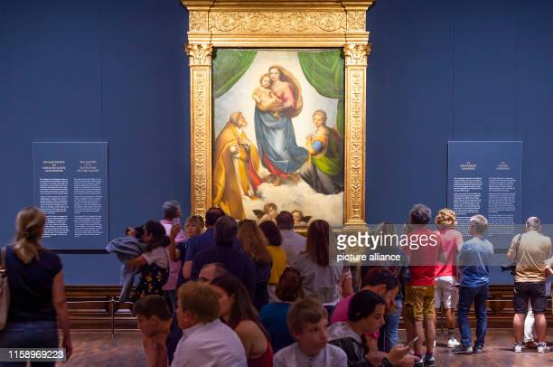 "August 2019, Saxony, Dresden: Numerous visitors look at Raphael's work ""Sistine Madonna"" in the exhibition ""Highlights of the Old Masters Picture..."