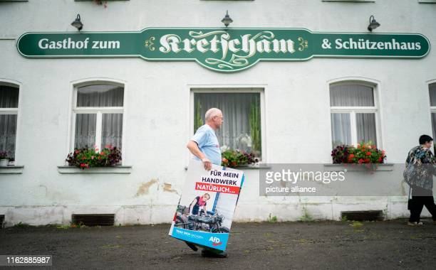A helper carries election posters to an AfD election campaign event for the Saxon state election In Saxony a new state parliament will be elected on...