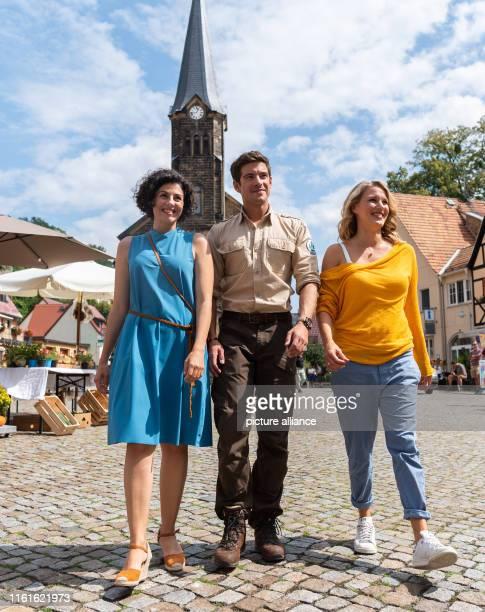 August 2019, Saxony, Stadt Wehlen: The actresses Liza Tzschirner and Eva-Maria Grein von Friedl walk across the marketplace with Philipp Danne, actor...