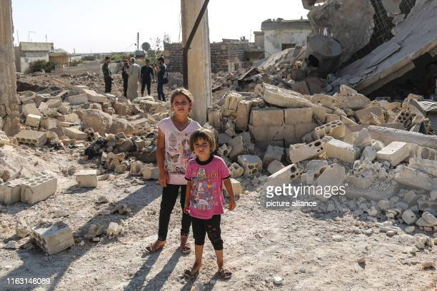 August 2019, Syria, Idlib: Girls stand inside the damage following a reported air strike in the area of Tallmannis in Syria's northern Idlib...