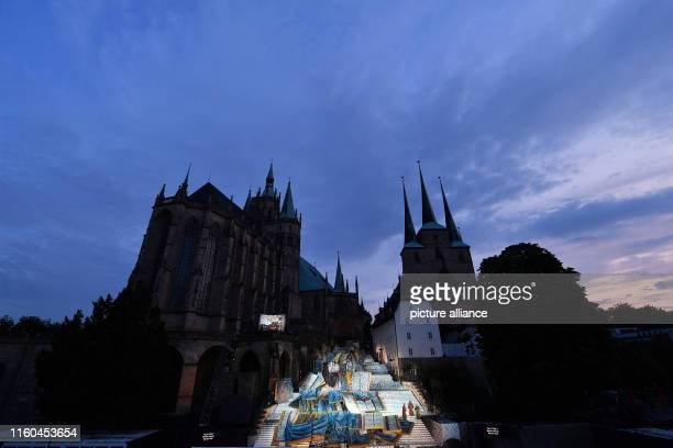 On the cathedral steps below Mariendom and Severikriche rehearsals are held for the premiere of the musical The Name of the Rose based on the...