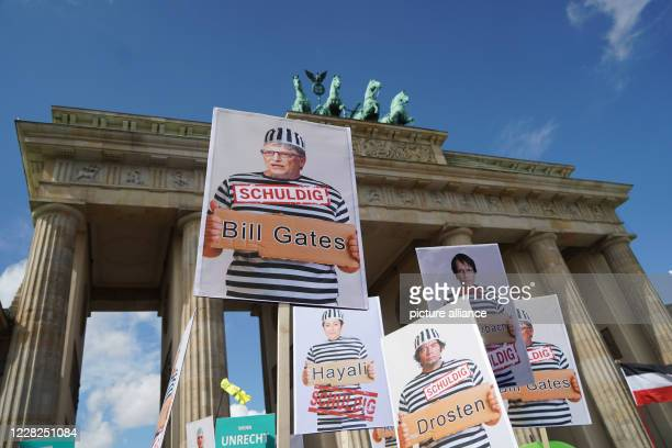 August 2020, Berlin: Participants of a demonstration against the Corona measures hold signs at the Brandenburg Gate with photomontages by Bill Gates...