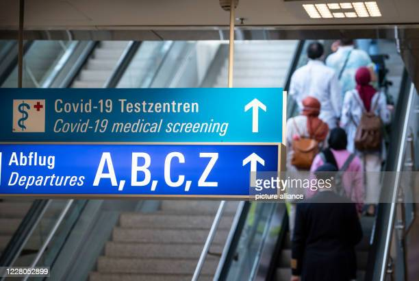August 2020, Hessen, Frankfurt/Main: A sign in the arrivals area of Frankfurt Airport shows the way to departures and the Covid 19 test centres....