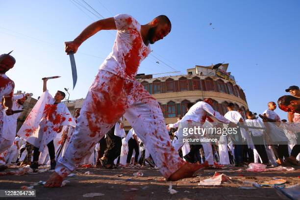 August 2020, Iraq, Baghdad: Shiite Muslims men hit their head with swords, which known as Tatbir, during a ritual ceremony on the day of Ashura in...