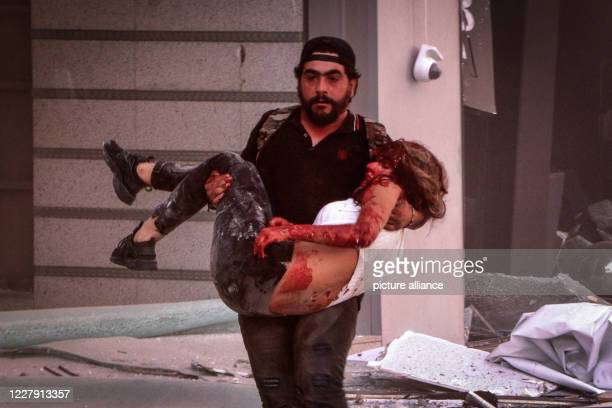 August 2020, Lebanon, Beirut: A man carries away an injured person following a massive explosion in Beirut's port that rocked the whole city. Photo:...
