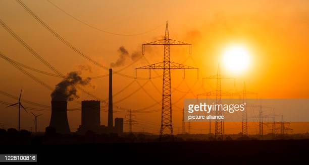 August 2020, Lower Saxony, Hohenhameln: The sun rises behind the Mehrum coal-fired power station and high-voltage lines in the Peine district....
