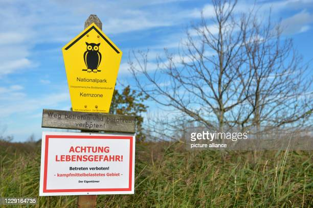 """August 2020, Mecklenburg-Western Pomerania, Darß: """"Attention, danger to life! no trespassing! area contaminated with weapons"""" is written on a board..."""