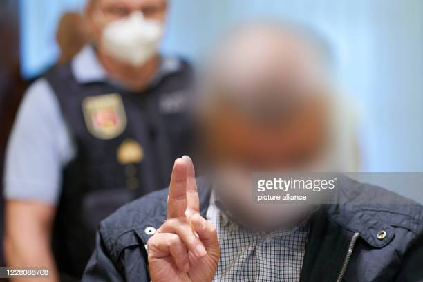 August 2020, Rhineland-Palatinate, Koblenz: A defendant makes the victory sign when entering the courtroom of the Higher Regional Court. The...
