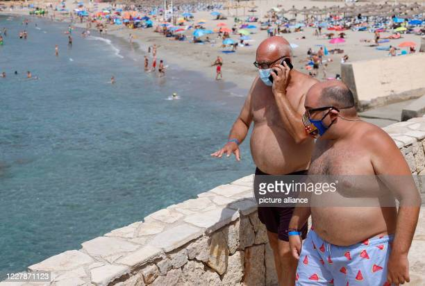 August 2020, Spain, Paguera: Christian and Mateo from Palma wear a mouth and nose cover on the beach on the island of Mallorca. Photo: Clara...