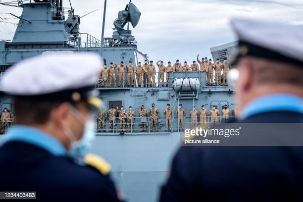 """August 2021, Lower Saxony, Wilhelmshaven: The crew waves from aboard the frigate """"Bayern"""", which is setting off on a training voyage lasting several..."""