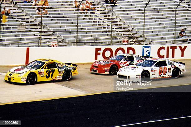 Robert Huffman in a Toyota leads the Pontiac of Gary Moore and the Mercury of Cam Strader during the Pabst Blue Ribbon 150 NASCAR Goody's Dash series...