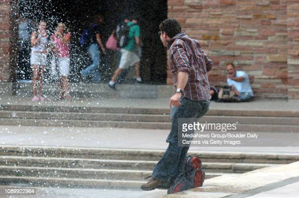 August 22 2005 / Boulder Colo / Brandon Adams a senior at the University of Colorado jumps back after the wind shifted the water from the Dalton...