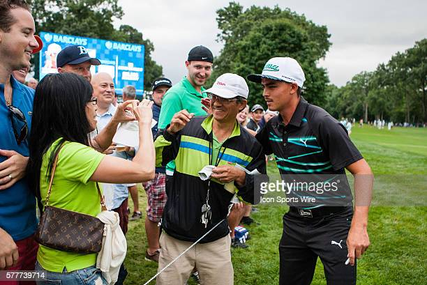 Rickie Fowler gives a fan an autographed glove after hitting him on his approach shot on 18 during the second round of The Barclays at Ridgewood...