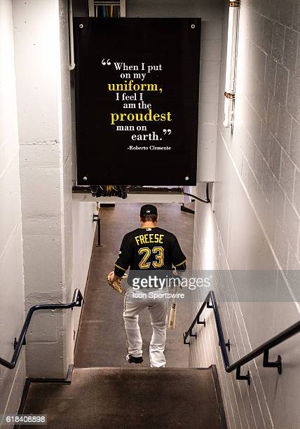Pittsburgh Pirates third baseman David Freese touches a sign honoring Roberto Clemente on his way to the dugout before the start of the game between...