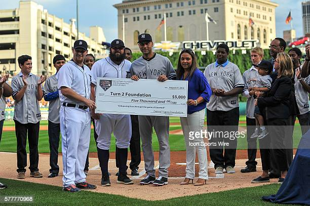 Detroit Tigers relief pitcher Phil Coke and Detroit Tigers relief pitcher Joba Chamberlain stand with a donation to New York Yankees shortstop Derek...