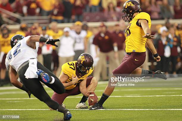 August 28 2014 Gophers kicker Ryan Santoso kicks the extra point as punter Peter Mortell holds the ball at the Minnesota Gophers game versus Eastern...