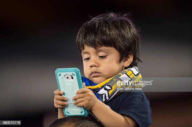 A young fan prefers his phone over an MLS game between the San Jose Earthquakes and the Los Angeles Galaxy at Avaya Stadium in San Jose CA