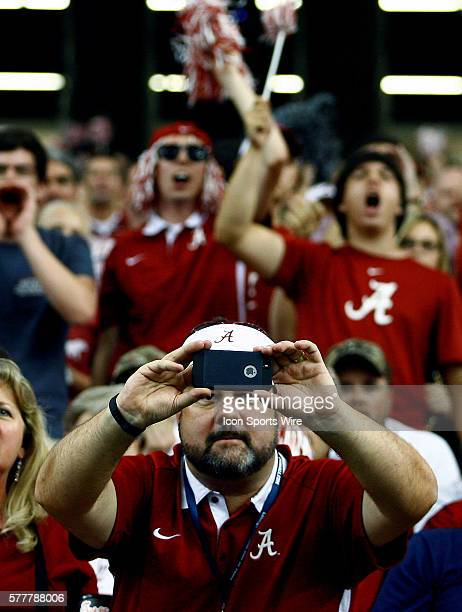An Alabama Crimson Tide fan snaps a photo during the fourth quarter Alabama Crimson Tide defeated the West Virginia Mountaineers 3323 at the Chick...