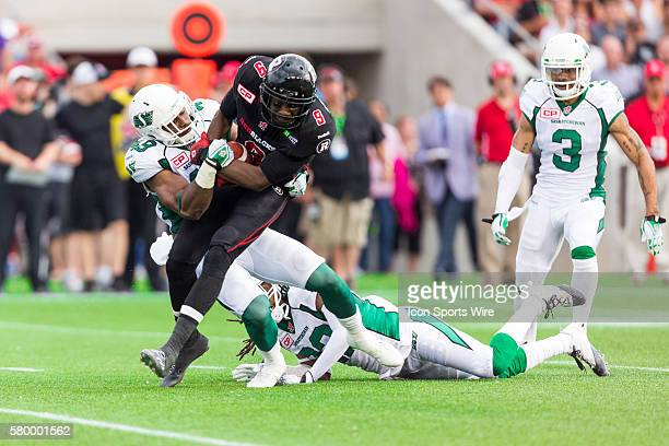 Ottawa RedBlacks Ernest Jackson attempts to break a tackle by Saskatchewan Roughriders Jeff Knox Jr during Canadian Football League action between...