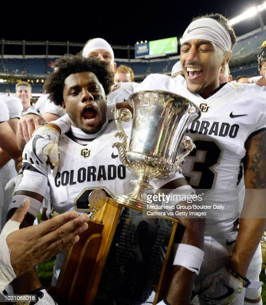 August 31 University of Colorado's Ronnie Blackmon left and Derrion Rakestraw take off with the Centennial Cup after beating Colorado State...