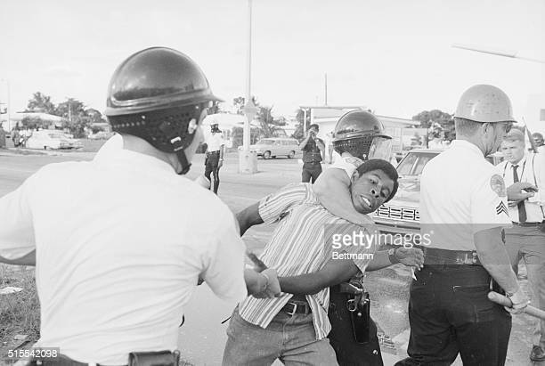 August 8, 1968 - Miami: Miami policemen, one holding the man's arm and the other with an arm lock on his neck, drag away a Negro youth during a clash...
