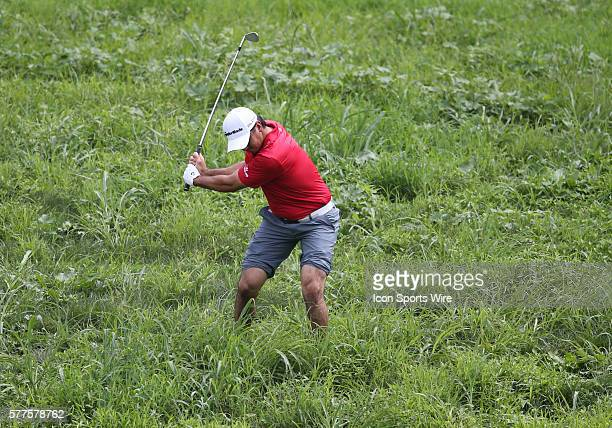 Jason Day has to roll up his pants and remove his socks and shoes as he crosses a creek to hit an errant shot during the third round of the PGA...
