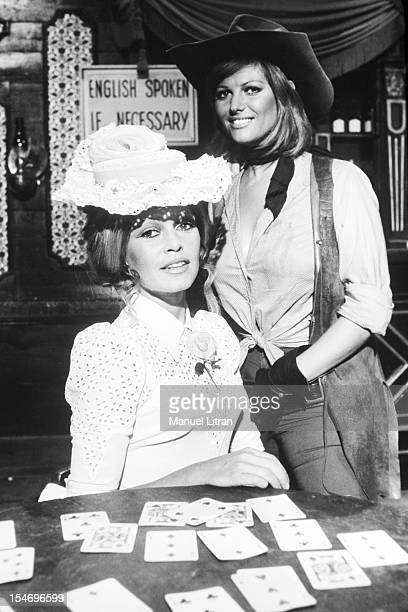 August 9 Brigitte Bardot and Claudia Cardinale pose together in costume in front of the Wild West of playing cards while shooting the film 'The...