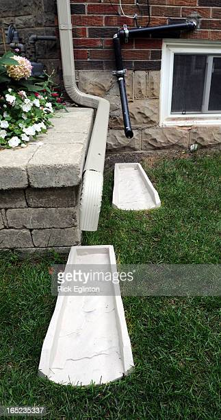 August1909RE4158375Home retrofitting to prevent basement floodingDownspout and black pipe from sump pump run water away from houseRick Eglinton...