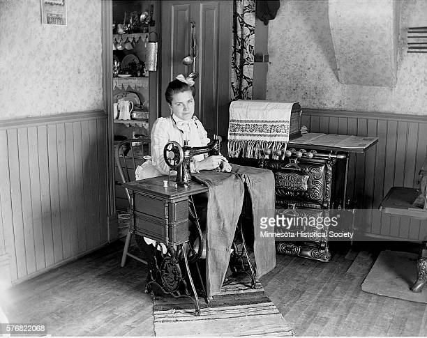 Augusta Munson sews a pair of jeans on an old Singer sewing machine