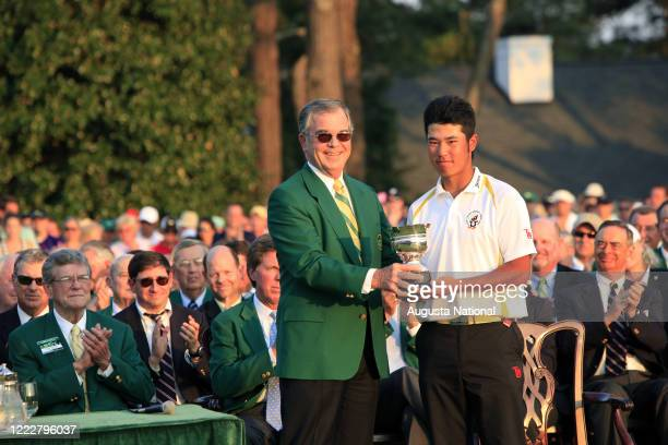 Augusta National Golf Club and Masters Tournament Chairman Billy Payne, left, hands the Low Amateur Silver Cup to Masters participant Hideki...