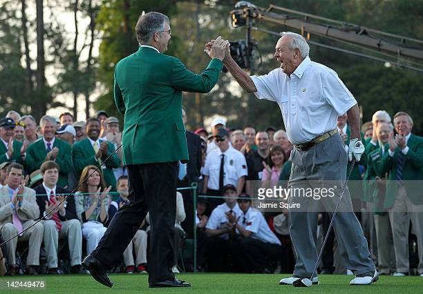 Augusta National Golf Club chairman William Porter Payne high fives honorary starter Arnold Palmer after his tee shot on the first hole during the...