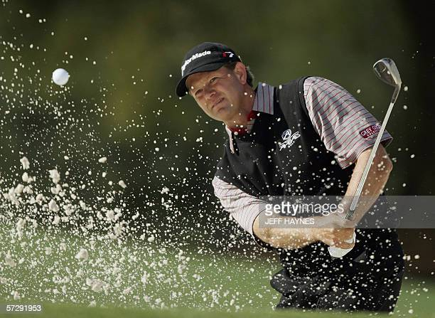 Augusta, UNITED STATES: Retief Goosen of South Africa hits out of a sand trap on the 18th hole 09 April 2006, during the rain delayed third round for...