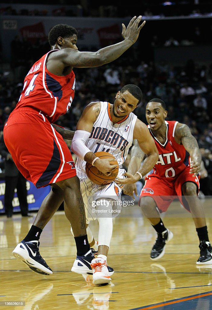 D.J. Augustin #14 of the Charlotte Bobcats dribbles through teammates Marvin Williams #24 and Jeff Teague #0 of the Atlanta Hawks during their game at Time Warner Cable Arena on January 6, 2012 in Charlotte, North Carolina.