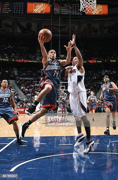D J Augustin of the Charlotte Bobcats drives to the basket against Maurice Evans of the Atlanta Hawks at Philips Arena on November 21 2008 in Atlanta...