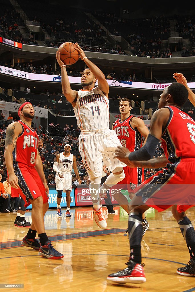 DJ Augustin #14 of the Charlotte Bobcats shoots against Deron Williams #8 and MarShon Brooks #9 of the New Jersey Nets during the game at the Time Warner Cable Arena on March 4, 2012 in Charlotte, North Carolina.
