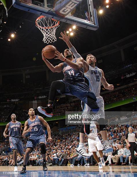 J Augustin of the Charlotte Bobcats shoots against Hedo Turkoglu of the Orlando Magic on April 1 2011 at the Amway Center in Orlando Florida NOTE TO...