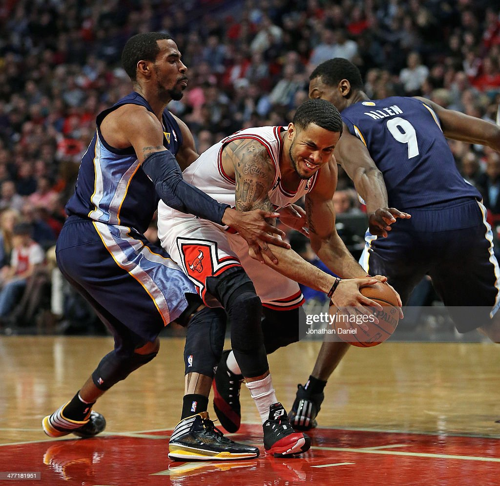 D.J. Augustin #14 of the Chicago Bulls fights his way between Mike Conley #11 (L) and Tony Allen #9 of the Memphis Grizzlies at the United Center on March 7, 2014 in Chicago, Illinois. The Grizzlies defeated the Bulls 85-77.