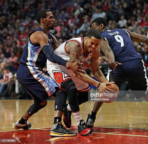 J Augustin of the Chicago Bulls fights his way between Mike Conley and Tony Allen of the Memphis Grizzlies at the United Center on March 7 2014 in...