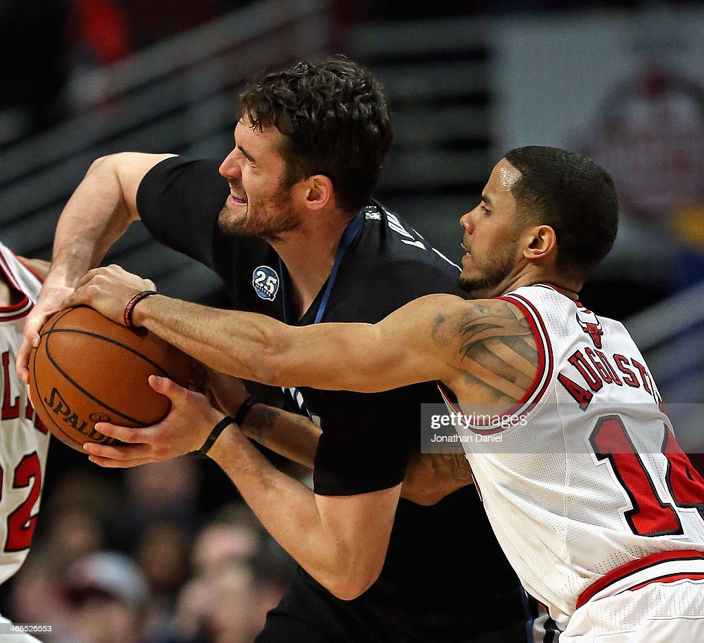 D.J. Augustin #14 of the Chicago Bulls fouls Kevin Love #42 of the Minnesota Timberwolves at the United Center on January 27, 2014 in Chicago, Illinois. The Timberwolves defeated the Bulls 95-86.