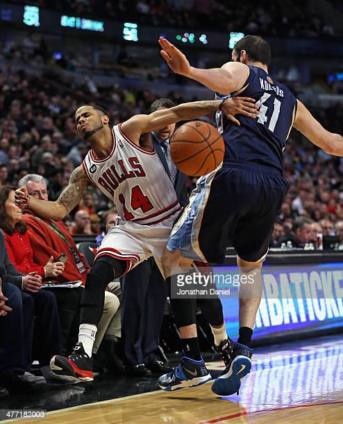 J Augustin of the Chicago Bulls is fouled by Kosta Koufos of the Memphis Grizzlies at the United Center on March 7 2014 in Chicago Illinois The...