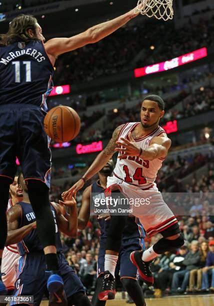 J Augustin of the Chicago Bulls passes around Josh McRoberts of the Charlotte Bobcats at the United Center on January 11 2014 in Chicago Illinois The...