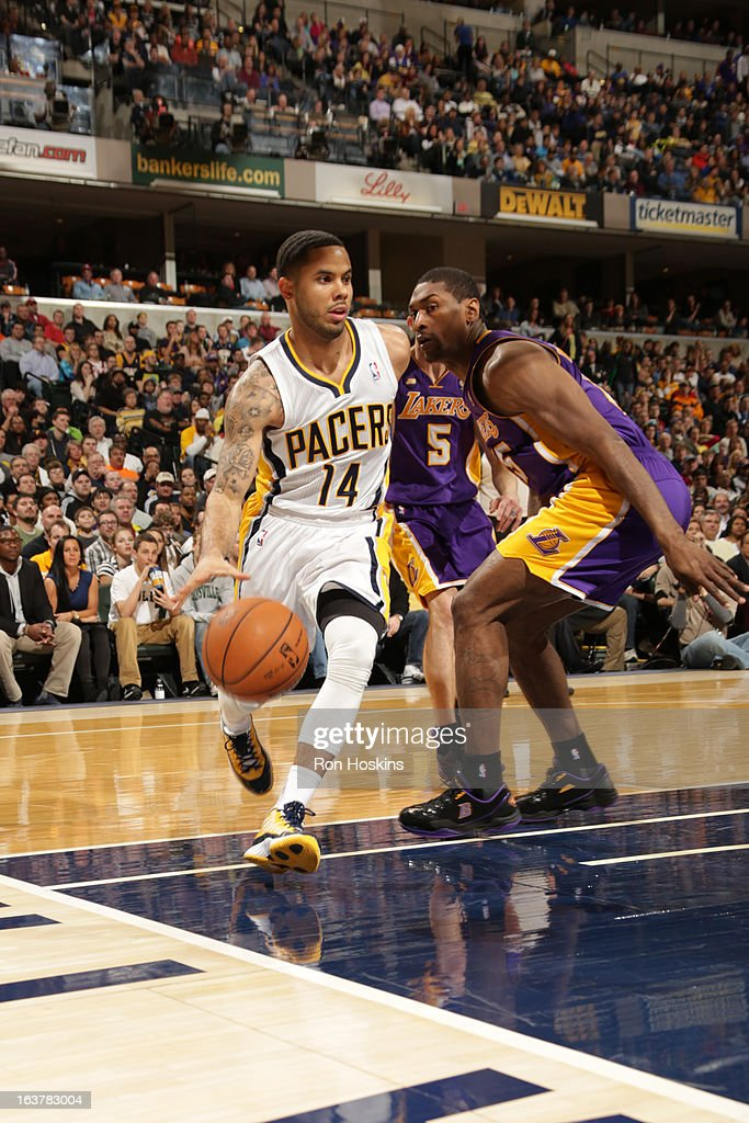 D.J. Augustin #14 of the Indiana Pacers drives baseline against Metta World Peace #15 of the Los Angeles Lakers on March 15, 2013 at Bankers Life Fieldhouse in Indianapolis, Indiana.